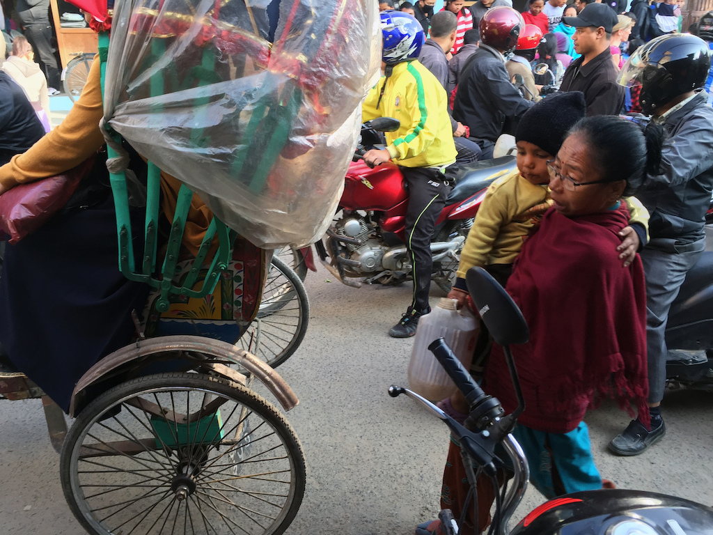 A woman and child with their precious fuel in the busy streets of Kathmandu