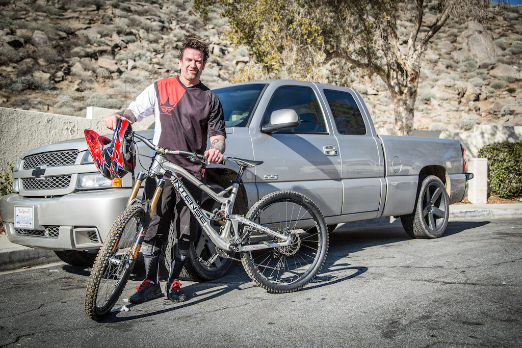 "Palmer poses with the one-off Aluminum Socom in front of his new Daily Driver, a 2006 Chevrolet (Silverado) SS.  The bike is a 6"" travel bike with M16 linkage."
