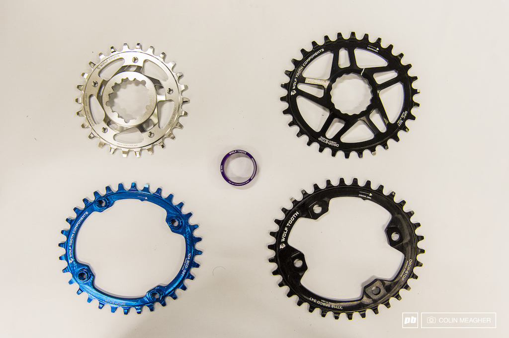 "Located about 4 minutes from QBP HQ here in Minneapolis is Wolf Tooth. They cut their teeth on making narrow wide chain ring options very early in the SRAM 1 x 11 game and their two latest offerings keep in that vein: Eliptical wide narrow (called ""Drop Stop"") chainrings for better pedaling ergonomics and stainless steel Drop-Stop chainrings for increased durability. They also have nice anodyzed headset spacers. What we see here are (clockwise, top left): 28T SRAM Direct Mount 426 stainless Drop Stop chainring, an elliptical alloy 30T Drop-Stop Race Face compatible direct mount  (Cinch) chainring, an XT compatible 34T Drop-Stop alloy 96 BCD chainring, and an anodyzed blue 32T 104 BCD Drop-Stop elliptical ring. Why Elliptical? Reutedly, elliptical rings deliver a smoother cadence for more reliable power transfer."