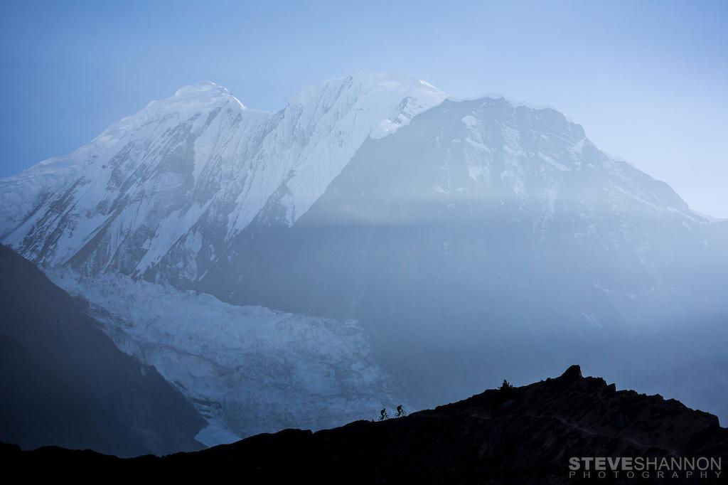 Mountain bikers silhouetted against the massive Himalayan peak, Gangapurna (7455m).
