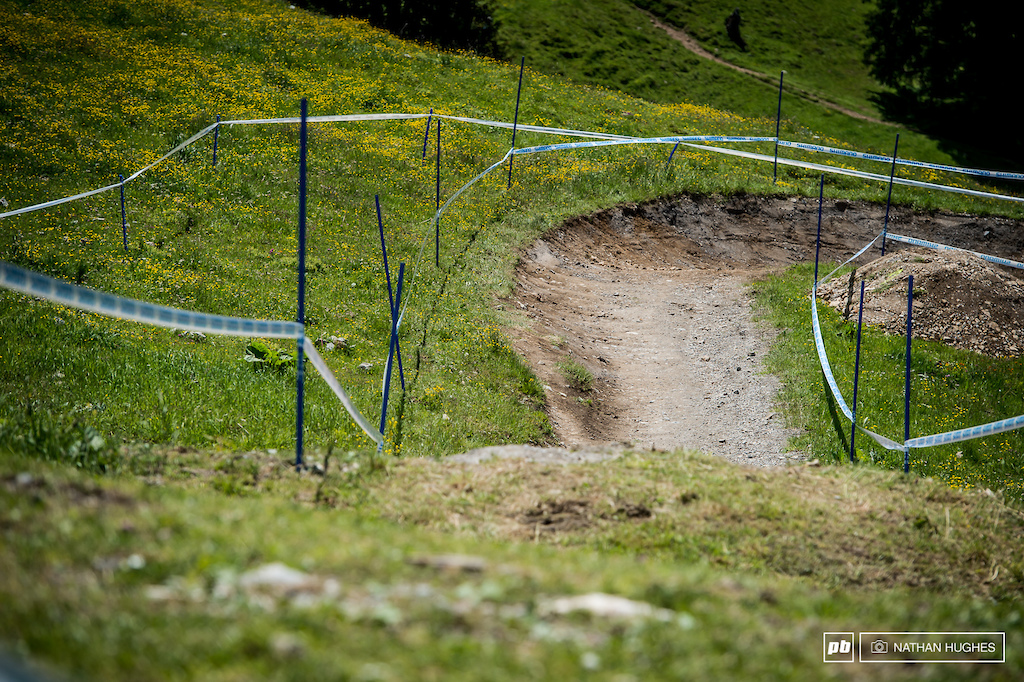 The new start comes in at an angle and leaps over a berm into the bikepark track for a series of berms instead of the old mix of off camber rocks and grass.