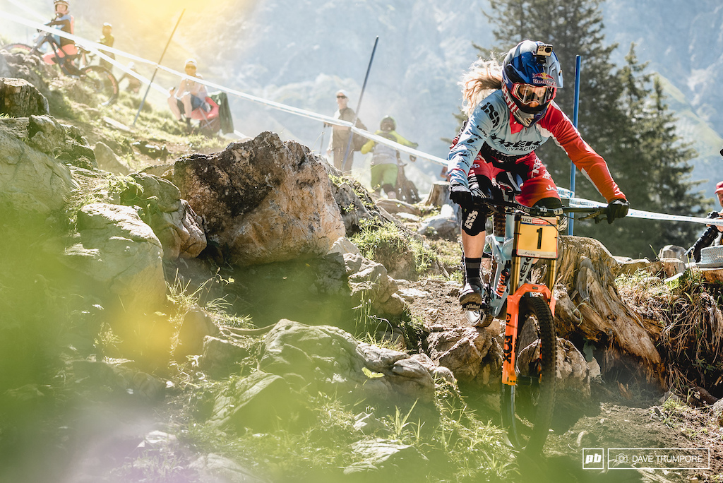 Rachel Atherton takes the straight line through the rocks, while many other cut to the riders left to get a better line into the switchback below.