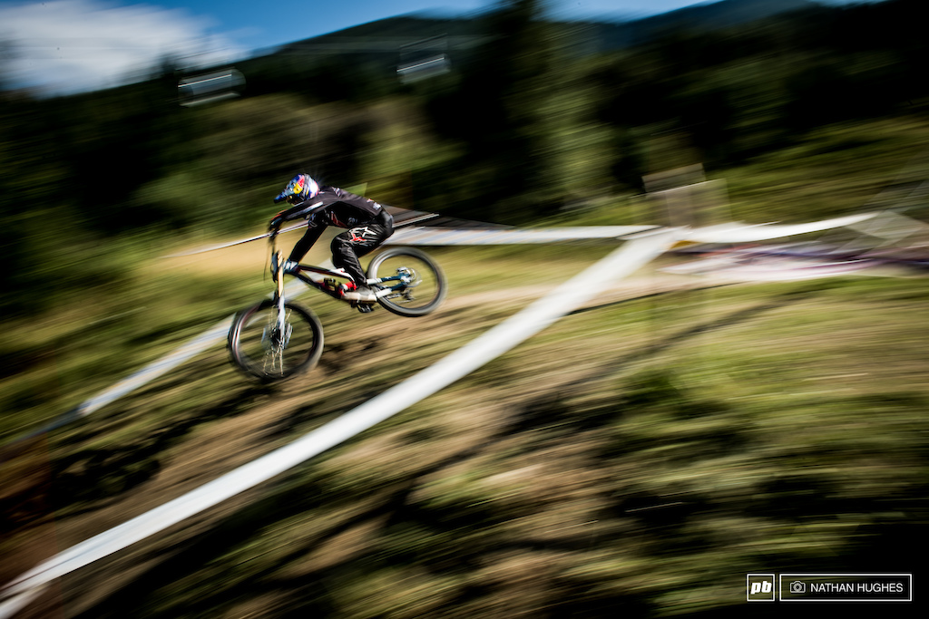 Aaron Gwin flipping the warp switch up above the woods.