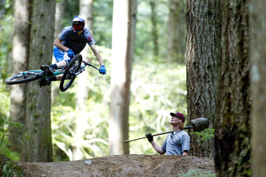 Brandon Semenuk hits a jump on Half Nelson while trailbuilder Ted Tempany looks on. Photographer John Gibson