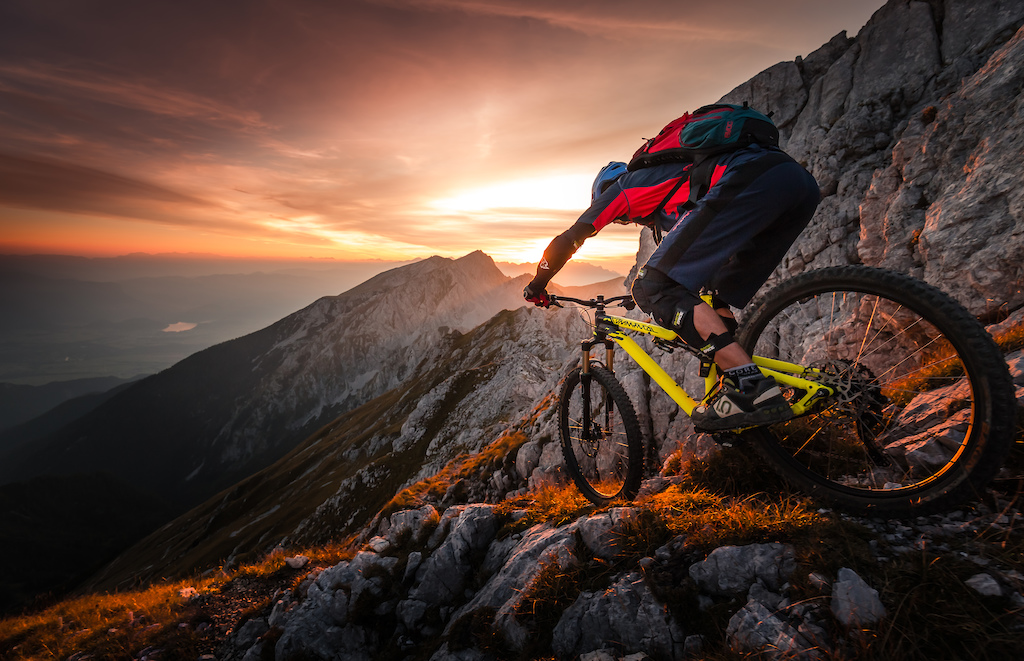 For a long time we planned this steep technical mtb descent from 2k high peak in the Alps which we visited mostly in the winter. We start our descent just before sunset when the light was warmer and softer. Lake Bled can be seen in the background.