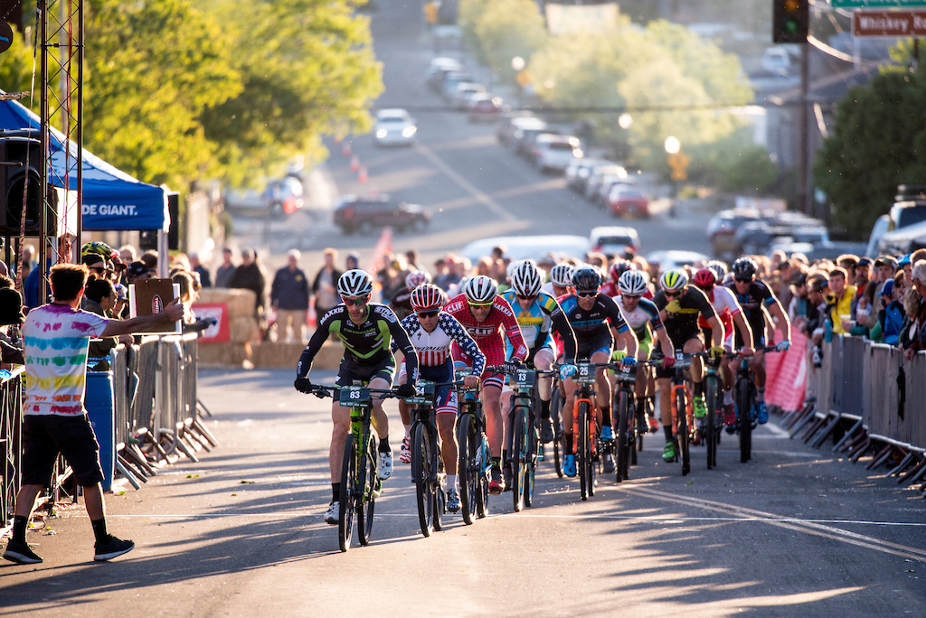 The pro mens Fat Tire Criterium moves through the starting gate as the sun sets over Prescott Friday.