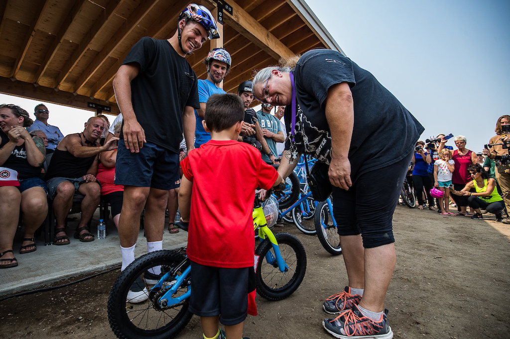 Finn Isles smiles as he hands over a fresh new bike to a super stoked child as part of Pinkbike's share the ride program.