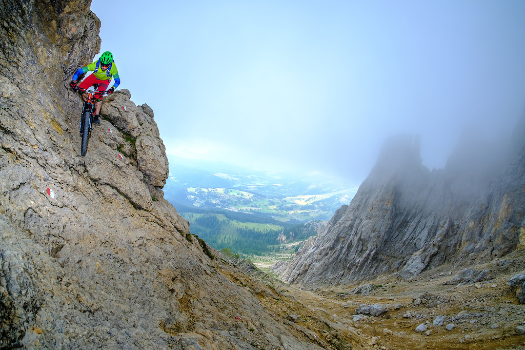 Riding down a steep rock section while descending from the Latemar Spitze in the Dolomites.