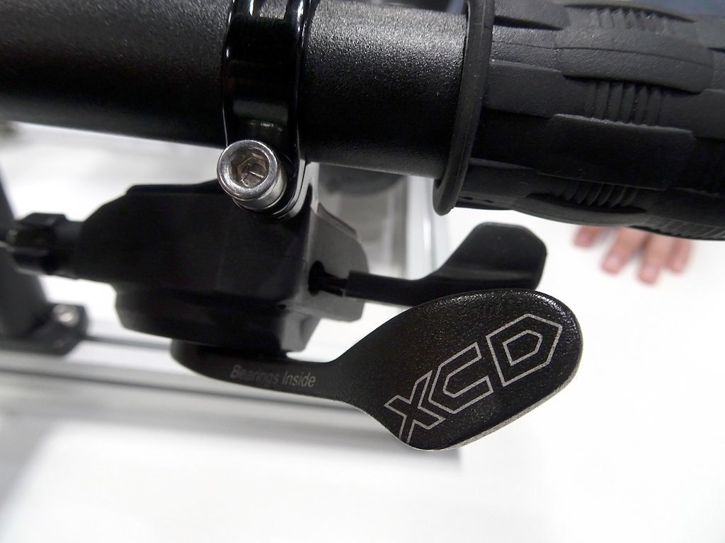 Microshift under-bar levers operate like first-gen Shimano - with a thumb paddle for downshifts and a finger trigger for upshifting.