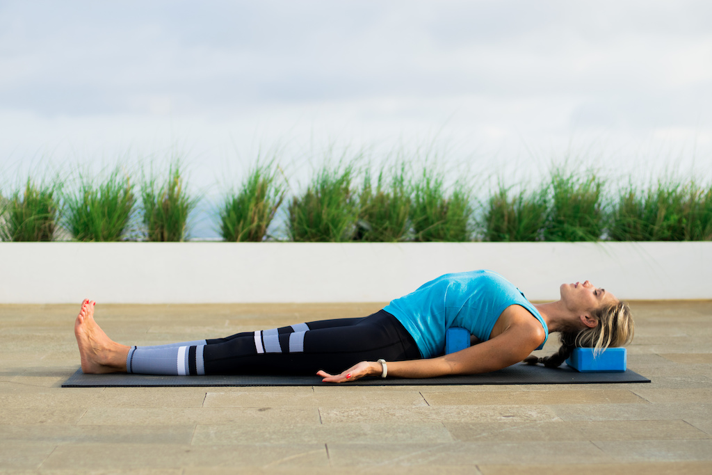 Supported Fish pose to relieve neck pain. Photo credit Paul Baker