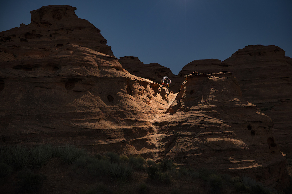 Thomas Vanderham riding slick rock lines in Southern Utah illuminated with remote strobe on drone heli.