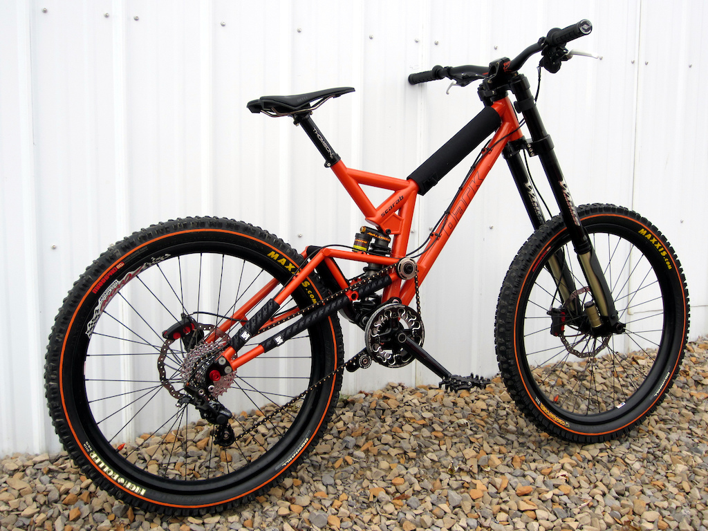 *FRAME: Dark Cycles Scarab  w/ Avalanche Chubbie 8.75x2.75 offset bushing *FORK: White Brothers Groove 200 DH  *WHEELS: Arrow Racing DHX rims laced to Atom Lab Pimplite hubs W/ DT spokes *TIRES:  Maxxis Mobster 2.7 F High Roller 2.5 R orange line *BRAKES:  Maguar Gustav DH 210 F / 190 R *SHIFTER:  Shimano Zee 10 *R/DER:  Shimano Zee 10 Rear Derailleur    *CASSETTE: SRAM 10 speed 11-32 Cassette PG1070 *CHAIN: Connex 10s Black Gold  *CRANKSET: Profile Racing 170 w/ 4 bolt spider *CHAINRING: RaceFace DH 36t  *GUIDE: Dark Cycles w/ bash ring Envy BOTTOM BRACKET: Profile Racing external *SEATPOST:  Thompson Elite 30mm black *SEATPOST CLAMP: Woodman Deathclamp  *SADDLE:  WTB High Tail Ti *GRIPS: Intense Lock On, Straitline endcaps black   *BAR:  Chromag Fubars OSX 25mm Rise and 780, 31.8 Black Tight Orange *STEM: Dark Cycles Cog & Ax 31.8mm   *HEADSET: Works Components 1 Deg *CABLES & HOUSING: Jagwire L3  *PEDALS:  Dark Cycles Arachnid Pedals