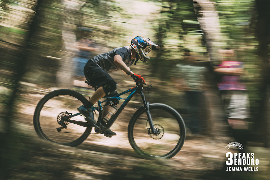 Braedan Trompetter of Dunedin flies through the lower sections of The OC as a bunch of hecklers look on in the 3 Peaks Enduro.