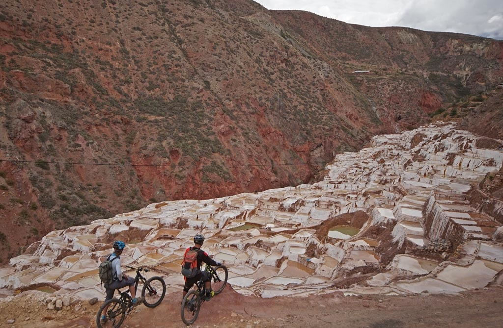 Holy Trails uses this route as a more chill day of riding and an opportunity to see more Inka History and partake in local culture. The town of Maras allows access to two archaeological Inka sites – the Moray Inka Ruins and the Maras Salt Ponds. We drive through Maras and were dropped off at 3800m at Misminay.  From there we ride through villages to view the Moray Terraces. These were built by the Inka and are thought to be research terraces where the Inka would plant different crops at different elevations and aspects to see how they would grow. This South side of the valley is considered drier then the North side which has the more glaciated peaks. It is perhaps this geological aspect that also helped to create the next archaeological site we passed through, the Maras salt mines.