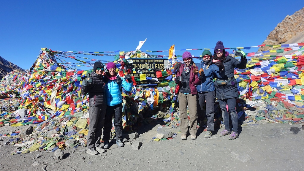 World Ride participants and guide Usha are all smiles after topping out on Thorong La Pass 5416m 17 769 ft the highest point on the Annapurna Circuit.