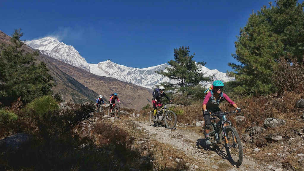 World Ride participants riding the Annapurna Circuit with views of Gangapurna Peak in the background.