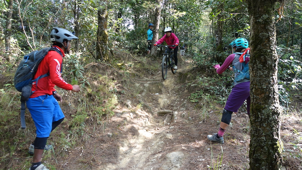 Nepali women practicing skills riding a technical drop at Nagarkot.