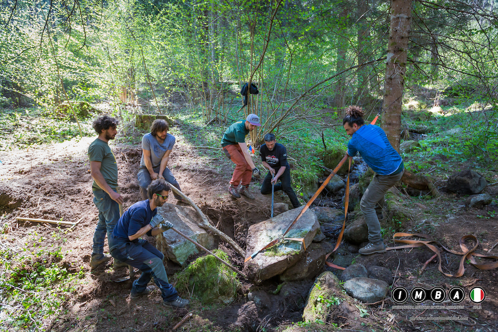 The rocky soil of Val di Sole hasn t been a problem for this group of trail builders from Sardinia here seen moving a flat rock that will become part of a stone bridge.
