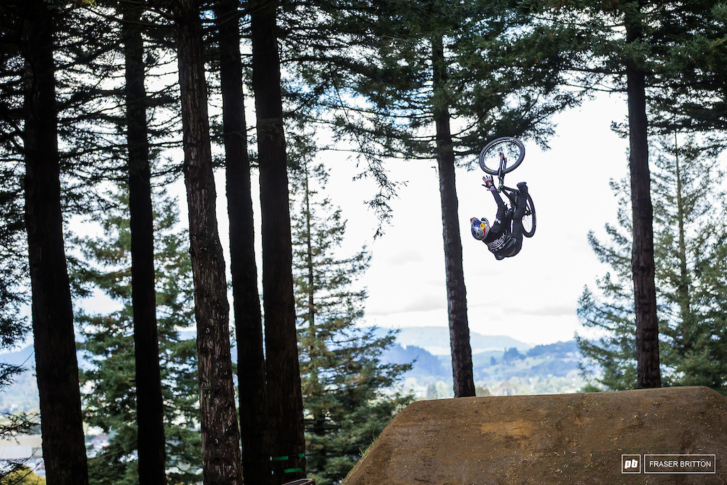 Szymon Godziek with a backflip bar spin over one of the wood to dirt features.