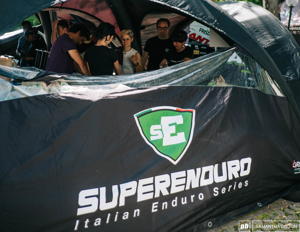 Superenduro sign on tent with eager riders.