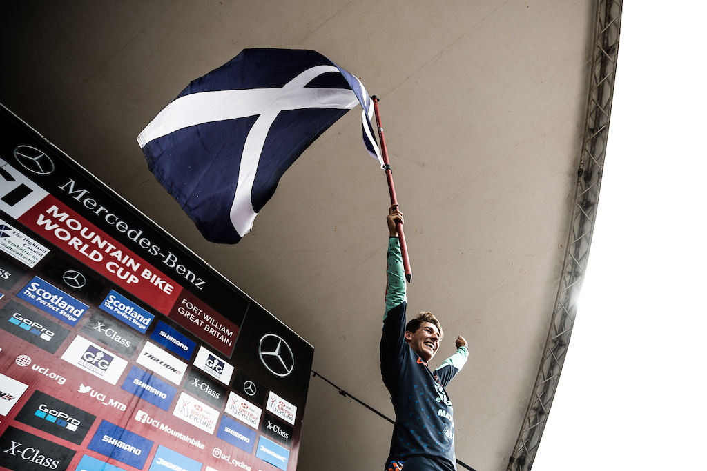 Reece hoisting the Saltire high in front of the home fans.