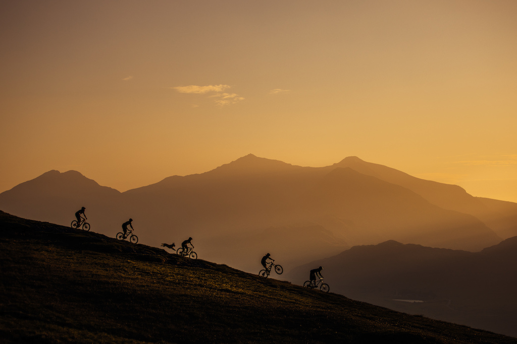 5 riders and Oakley the trail dog descending the mountain as the sun set over Snowdonia. Snowdon glowing in the background.