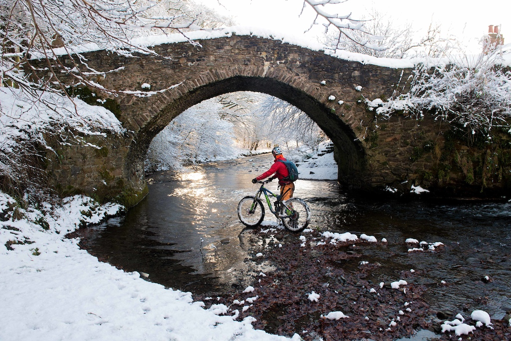 PICTURE BY GARETH EASTON PHOTOGRAPHY LTD. 07752 666 522 MICHAEL CLYNE FROM KELTIE IN FIFE ABANDONS THE HIGH TRAILS AND RESTS BY THE CUDDY BRIG ON LEITHEN WATER IN INNERLEITHEN AS SNOW FALL OF OVER 4 INCHES COVERS THE SCOTTISH BORDERS THIS MORNING AND MAKES RIDING THE HIGH MOUNTAIN BIKE TRAILS DIFFICULT.