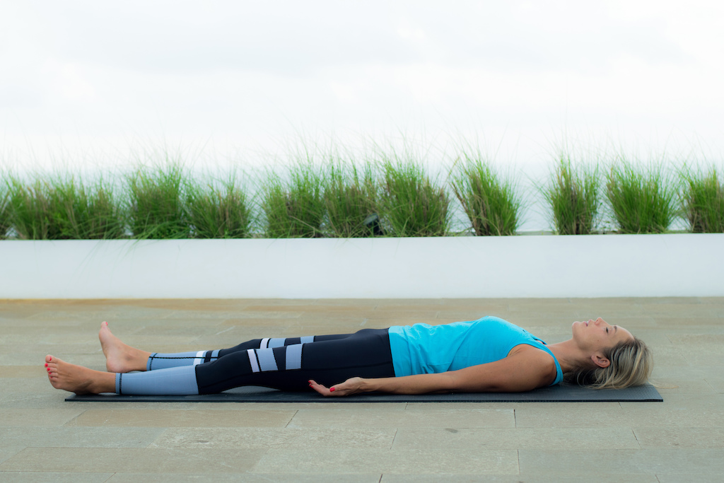 Corpse Pose for faster recovery pain relief and reduced muscle tightness. Photo credit Paul Baker
