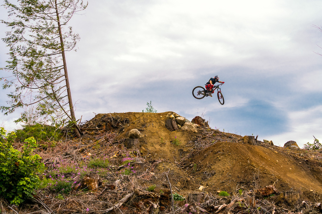 Kirt Voreis gets all tucked up over a step down on his mountain bike at Galbraith Mountain near Bellingham, Washington.