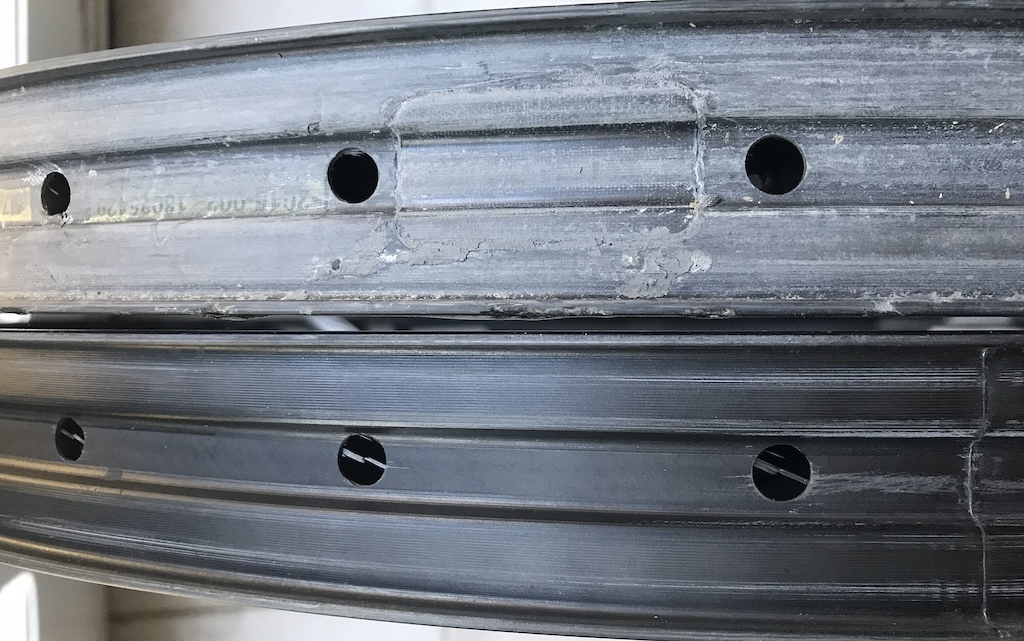 The rim in the bottom of the picture arrived with the spoke holes not perfectly aligned in the centre of the rim and had fibres sticking out.