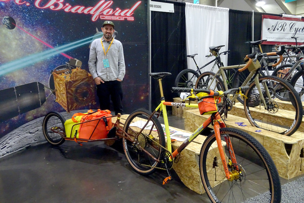 NAHBS 2019 W.H. Bradford Designs builder Brad Hodges poses with his Island Hopper - a hardtail trailer combination inspired and painted like the Helicopter by the same name in the TV series Magnum PI.