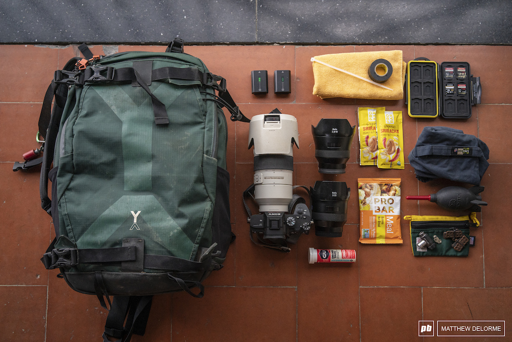 Matthew DeLorme's set up for a typical day of shooting EWS. NYA EVO Fjord 36 camera bag. NYA EVO is a relatively new bag company. Their philosophy is to make a rugged bag with as little environmental impact. The pack rides well and doesn't push up on the back of the helmet when the going gets steep.   Inside: Sony A7III,  Sony 70-200 2.8 G Master, Zeiss Batis 18 2.8, Zeiss Batis 25 2, Rocket Air ProBar Meal Bar, ProBar Siracha Peanut Butter, electrolyte tabs, electrical tape, quick link, brake pads, batteries, Co2 head, zip tie, tape, towel, lens coat rain cover. If the weather looks iffy, I'll bring rain gear as well.
