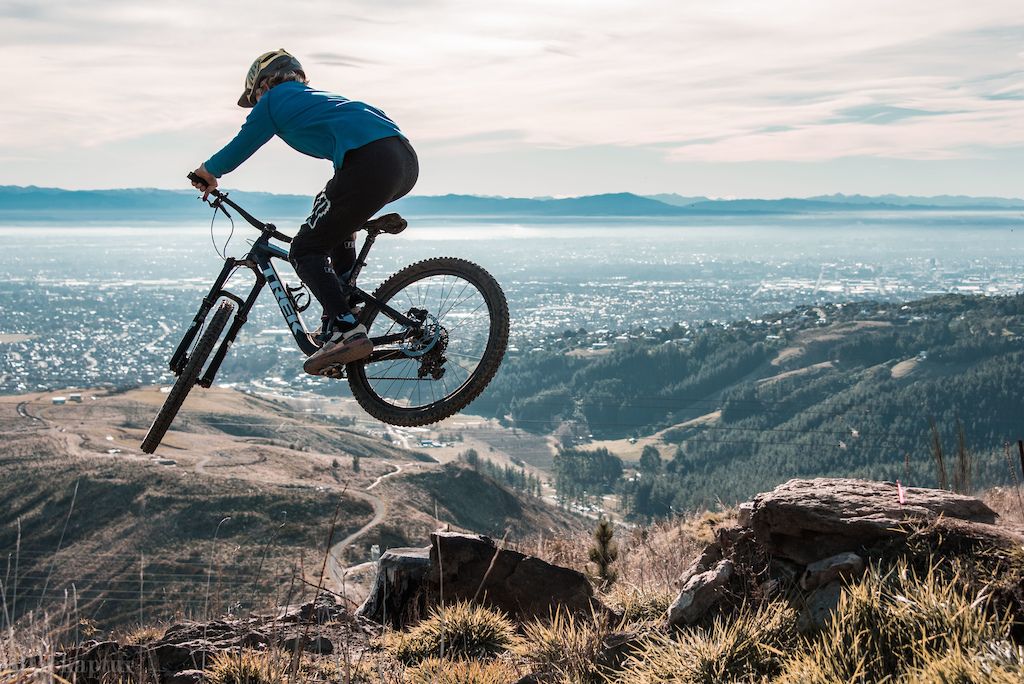 Lui steezes his way over small rock drop/step down on the amazing Throw the Goat trail at the Christchurch Adventure Park with views over Christchurch City and the Mountains in the distance...