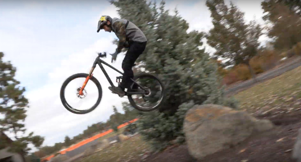 barspin off a rock while the kids play at the park