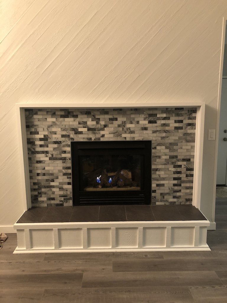 New fireplace surround polished marble with silver reflective glass bead grout.... oooo lalahhhh