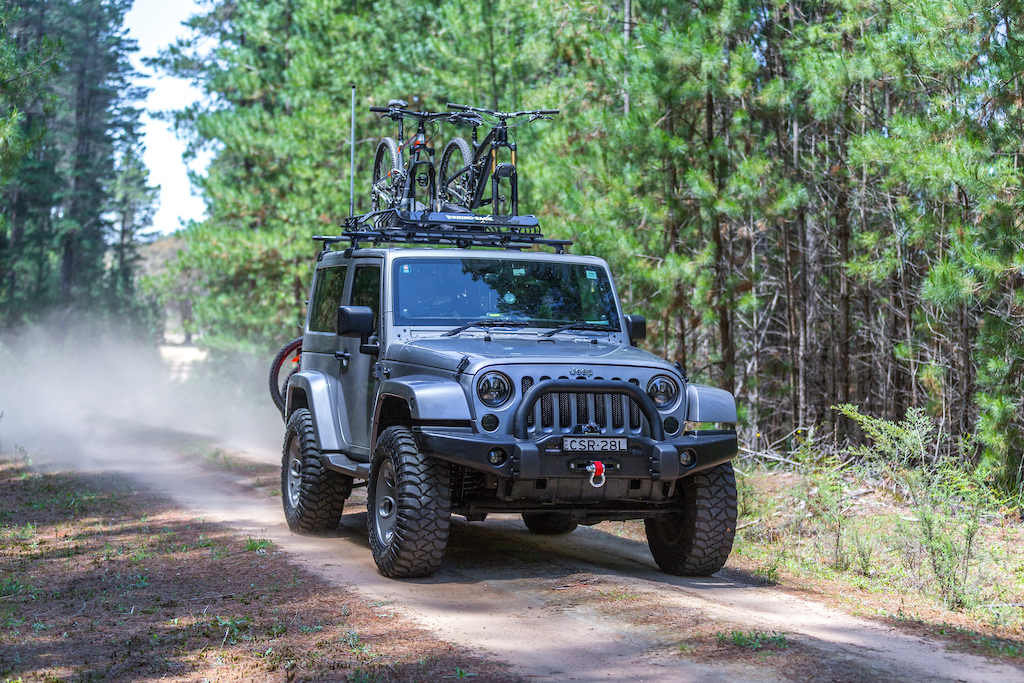 Rhino-Rack X-Tray Pro mounted on a Jeep with two mountain bikes on top.