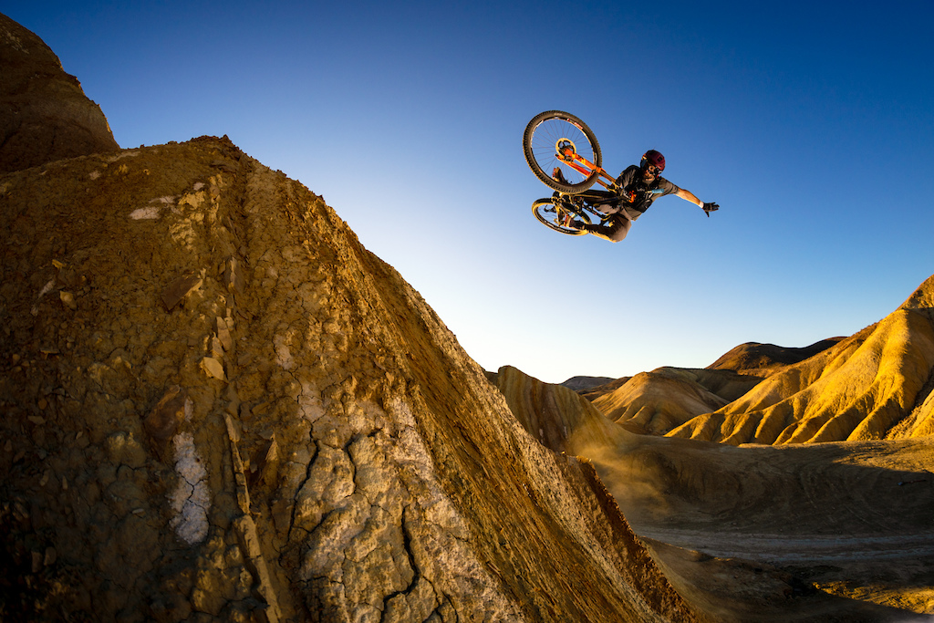Kirt Voreis does a one handed table in the California desert at sunset on his mountain bike.
