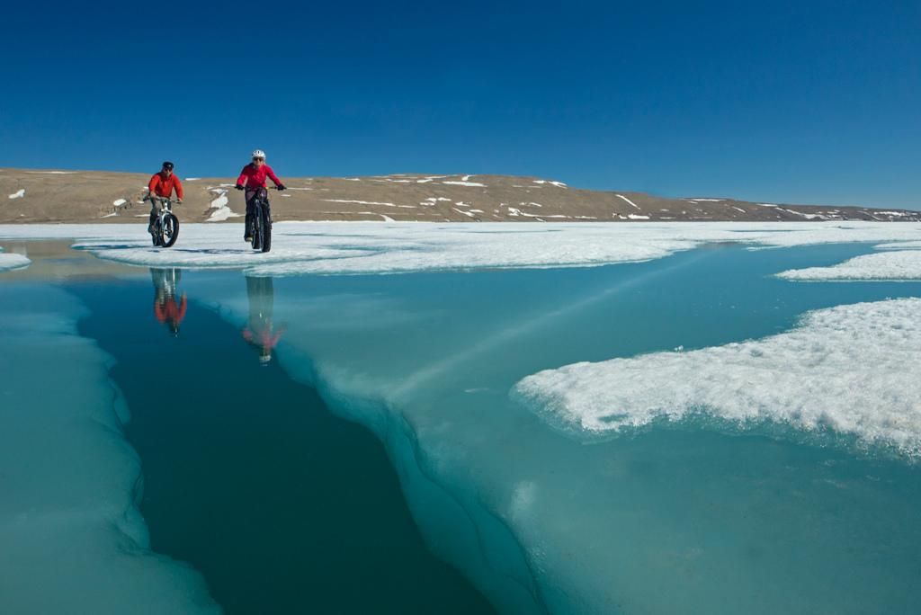 Biking on the floe edge sea ice of the Northwest Passage near Arctic Watch Wilderness Lodge Somerset Island Nunavut
