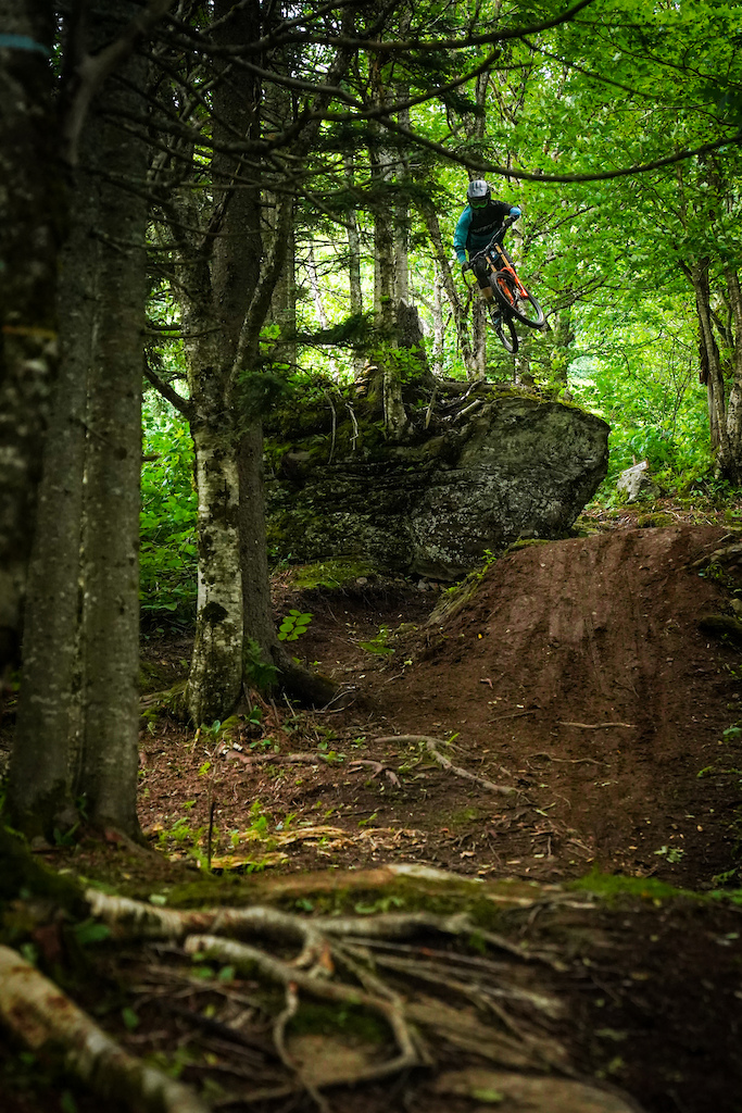 """Photo credit: Mark Clement.  Elliot Demers shows the way off the """"One Butter"""" drop at the top of Double Down trail (formerly """"One Love"""" trail) at Bolton Valley in early summer 2020."""