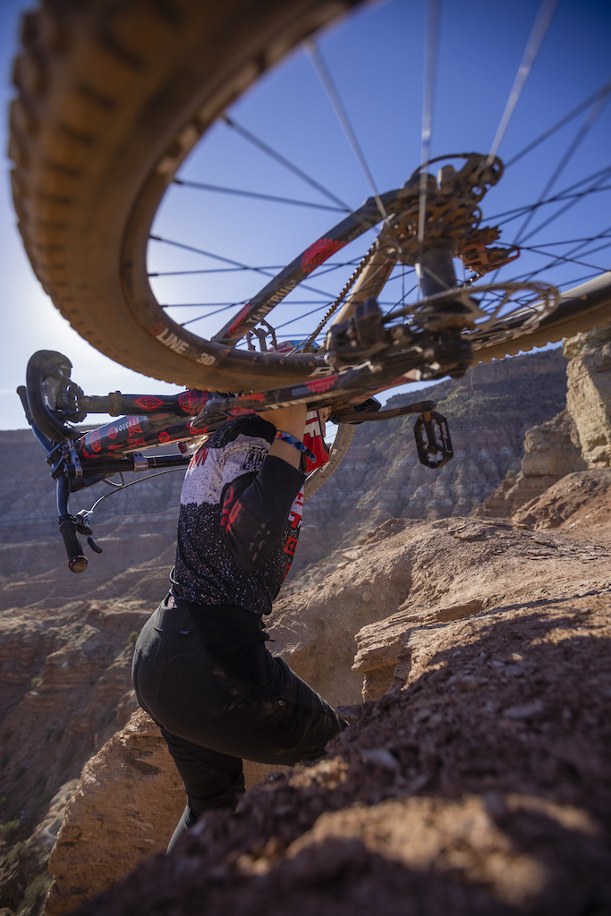Casey Brown hikes her bike to the top of her line at Red Bull Formation in Virgin Utah USA on 30 May 2021.