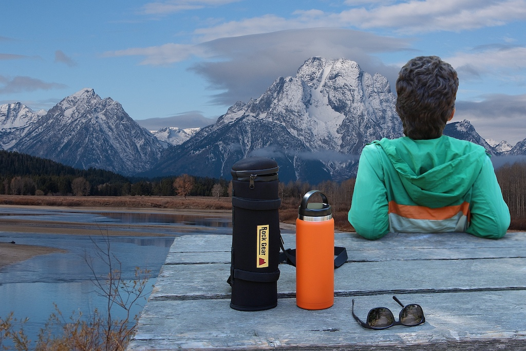 Rock Gear brand storage case and bottle on picnic table with Grand Tetons in the background.