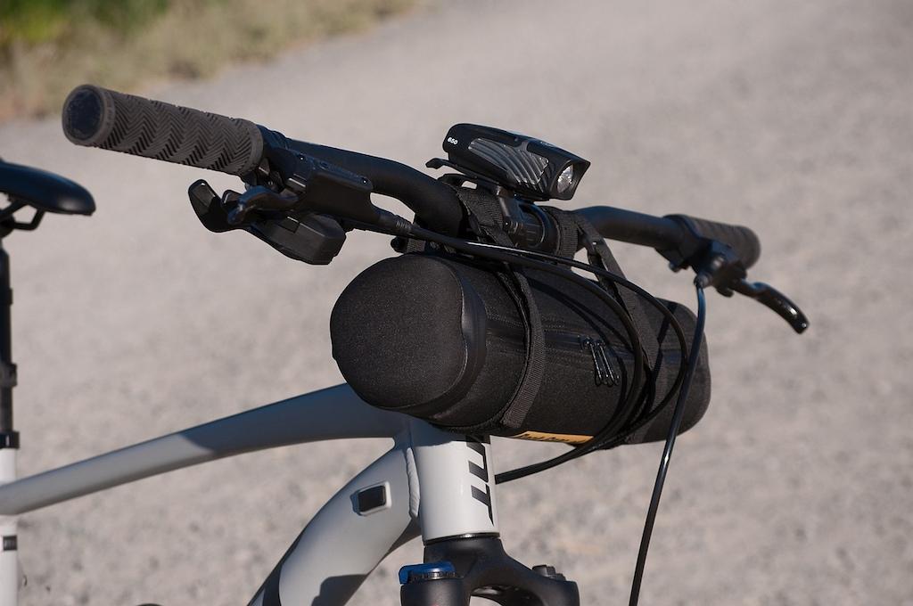 Rock Gear brand storage case on mountain bike handlebars. Side front view.