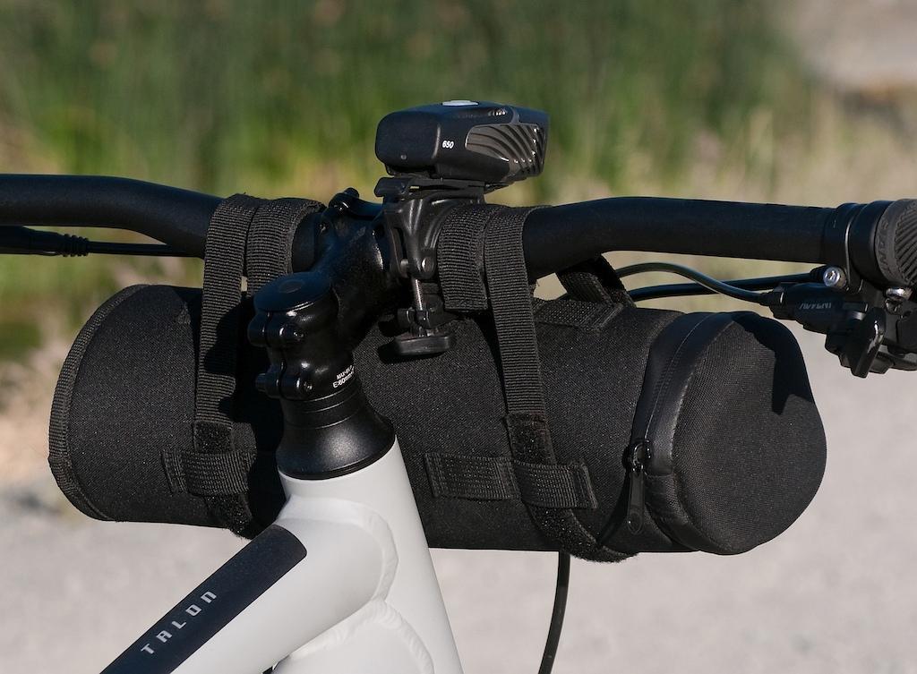 Rock Gear brand storage case on mountain bike handlebars. Rear view.