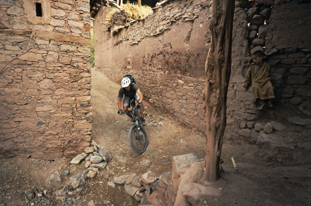<span style='font-size:12px'>Riding through the villages of the Atlas mountains means always having an audience, even if the audience is shy. Bikes are rare here, sights of bikes like Guillaume's Enduro even rarer.</span><br><br>The reward for our labor is a 600 meter downhill. We attack it with vigor, snaking down bits of singletrack on the way and in a fraction of the time it took to climb the pass we find ourselves pulling up to a halt in Amziri, listed in our guidebook as the most remote village in the High Atlas. Through the enveloping dusk we meander among the locals, all dressed in colorful embroidered dresses and headwear, before locating the solitary gite. It's the most basic place we've ever had the dubious pleasure in staying in, period. The bathroom resembles a 1980's Turkish prison cell, and for once I'm glad of the absence of electric light in the room. Berber dialect is the only language spoken here and over candlelight my companions dine on sinuousy meat while I stave of my vegetarian hunger with biscuits. It's a character building experience. The evening is short, the climb has seen to that, and for that I'm not unhappy. Tomorrow is a new day, another ride with a different set of challenges and rewards. When plans come together it can be a rewarding feeling. When they fall at a hurdle it can be a mental and physical challenge. Setting out on a trip like this takes certain courage: the courage to leave behind the comforts of home, to leave the security of knowing what's coming next, but the rewards are immense. The very next day we would find our planned sixty kilometers of twisting singletrack reduced to fifteen kilometers of hard slog and repeated river crossings, the trail having been washed away by the previous week's flooding. It's a day of hard earned dried fruit stops, but one that terminates in a comfy bed in a village of friendly people and excitable kids. Guillaume was right; all we needed was a bike and a backpack. In exchange, our reward 