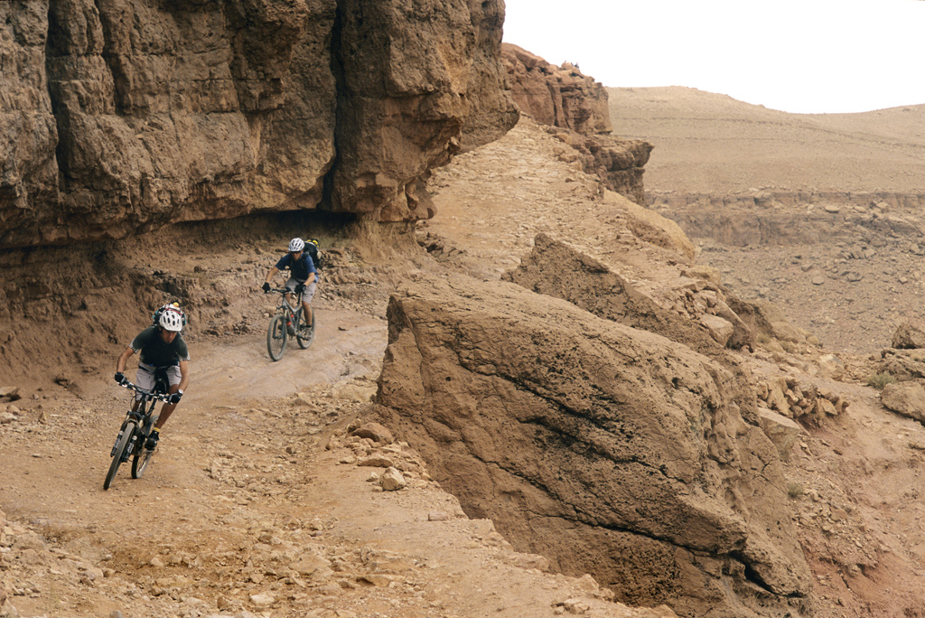 <span style='font-size:12px'>Even the jeep tracks in Morocco make fun riding. Mike and Guillaume put the hammer down on one of our rockier sections.</span><br><br>Our sleep is broken by the enigmatic early morning call to prayer, the unmistakable sound that punctuates trips to any Muslim country. We follow breakfast by wandering through the market, weaving between piles of vegetables and stepping over occasional discarded severed goats' hooves to stock up on dried fruit for the day's ride ahead of us. Above our heads it looks like a storm may be brewing, but no one can tell us if it will rain. The weather forecast here is