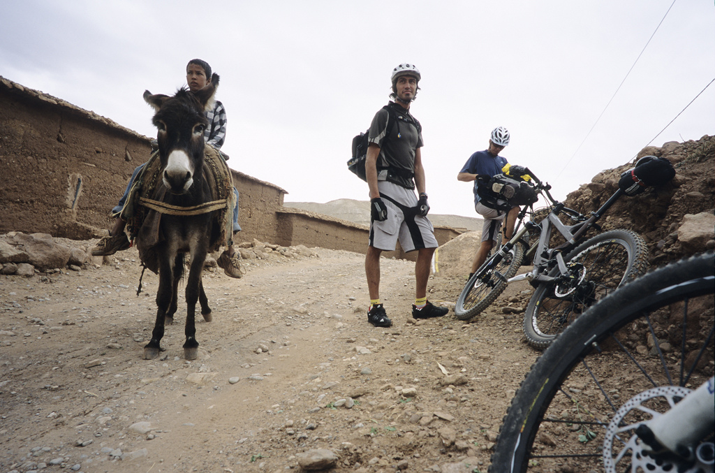 <span style='font-size:12px'>On day two we stumbled across this lad with his donkey. In pigeon French he managed to try to barter a swap, the donkey for a bike. We were tempted, but weren't sure how his father would be if he returned without the family's trusty beast of burden.</span><br><br>A recent starring role in the marvelous Roam mountain bike DVD has put Morocco squarely on the mountain bike map. The country, with its rugged mountain ranges and alien culture, is a one stop shop for adventure and serious riding possibilities and is accessed by a sub four hour flight from the UK. An Anglophile French friend and Chamonix riding pal, Guillaume, has ridden through Morocco's High Atlas mountains before, meaning that much of mine and Mike's preparation consists of badgering him to tell us what to expect. As we paw over maps, he fields our questions with ambiguous answers. 'We can try this way, but maybe we won't get through' he mumbles, tracing a finger along a dotted line. It is clear that although Guillaume has an idea for a route across, down, round and back over the Atlas mountains, a lot will be down to chance, or as I soon learn, 'Inshallah' (the will of God). Riding 4x4 tracks and sniffing out singletrack wherever we can find it, our XC trip will be a million miles from the freeride jaunt that appears in Roam, but we have a plan at least.