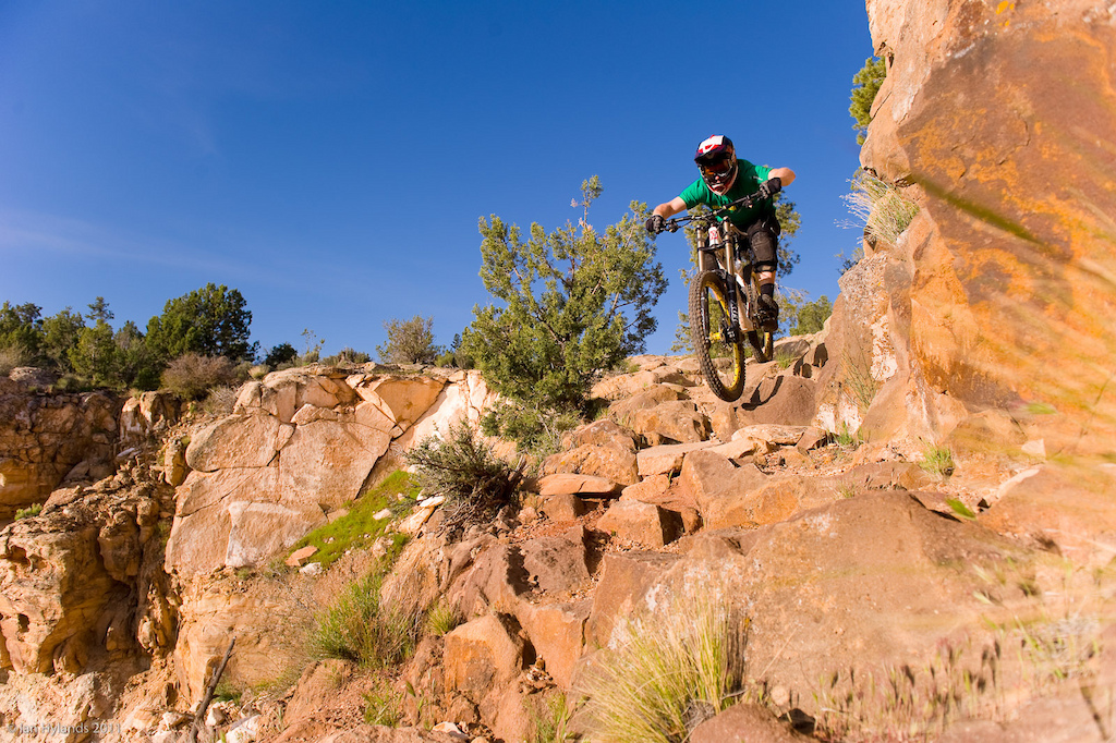 The Grafton trail is built on an old pioneer wagon road that wound its way up onto the mesa. Large sections of it were built by hand stacking hundreds if not thousands of large boulders against the cliff back in the 1800's. Here Kyle Thomas hits what's left of it at full DH race speed...