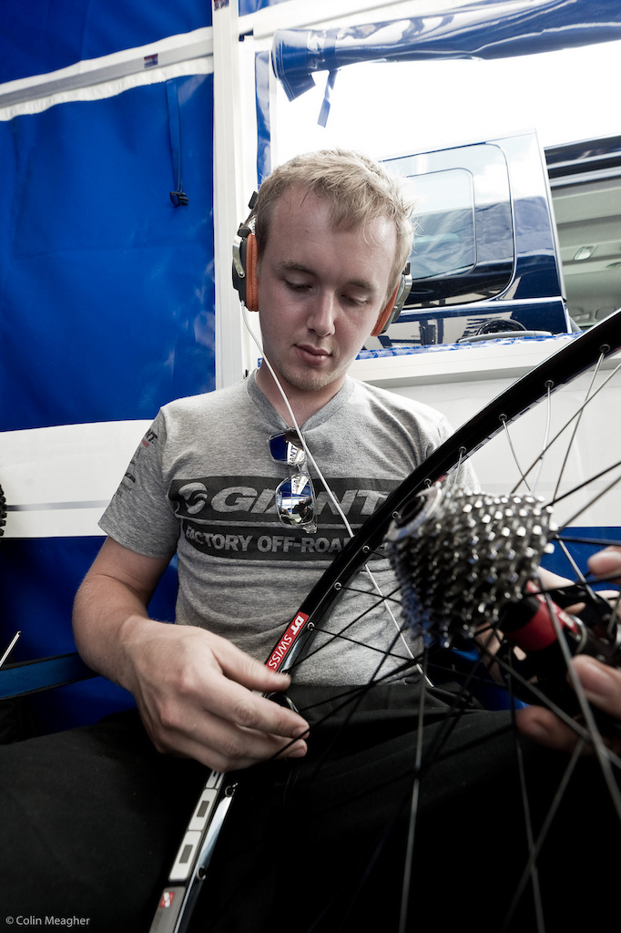 Given the roots and rocks on this track mechanics in the know are already lacing up sets of replacement wheels. Paul Miles of Giant Factory Racing is tucked away in the zen moment of building the perfect wheel. To house music.