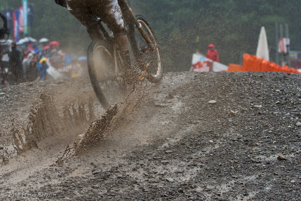 Andrew Neethling doesn t avoid the massive finish line jump puddle. Rotors sizzle like a motocross in the wet after racing this track.