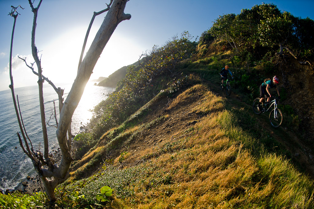 Seb Kemp and Katie Holden ride their bikes on a trail above the ocean near Robin's Bay in Jamaica at sunrise.